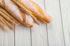 Two baguettes and ears of wheat on old white Royalty Free Stock Images