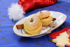 Two baked apples as Christmas dessert, red hat Royalty Free Stock Photos