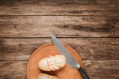 Two baked buns for breakfast on wooden background. Two baked bread buns served on platter with knife, on wooden table, top view. Food background with free space Stock Image