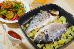 Two baked fish in pan, sauce and vegetables. Two baked fish in pan with sauce and  grilled vegetables Stock Photos