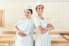 Two baker women standing proud in their bakery stock photos