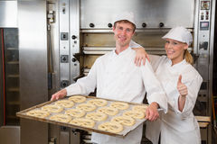 Two bakers with griddle full of pretzels Stock Images