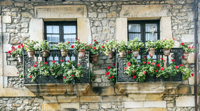 Two balconies with potted plants. And flowers located on a old stone façade in the Spanish town of Comillas north of Spain Royalty Free Stock Photography