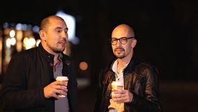 Two bald friends are walking in the evening in the city chatting, drinking coffee stock footage