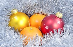 Two ball tinsel Mandarin. Three Christmas toys glass balls of red and yellow and two Mandarin lie in the shiny tinsel white Stock Photos