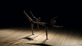 Two ballerina dancing on stage in the dark, slowly. Two ballerina dancing on stage in the dark, slow motion stock video