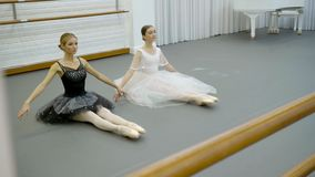 The two ballerinas do point toes sitting on the floor with feets together in the bright modern class. The one dancer wears black tutu and the other stock video footage