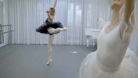 The two ballerinas are exercising the dance for performance in bright studio. The one graceful dancer wears white costume and her collegue is in eautiful black stock video