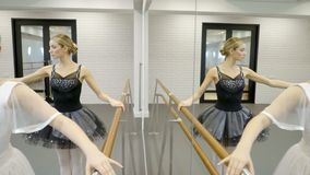 Two ballerinas are practiced by barre in ballet school. Young dancers stand in front of mirror, holding onto bar and tilting thin body to sides, raising hand stock video
