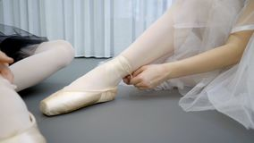 Two ballerinas tie pointe shoes on legs in ballet school. Young ladies bind satin ribbon of footwear to thin ankle, sitting on floor. Graceful dancers dressed stock video