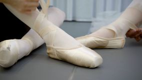 Two ballerinas are tying tape of pointe shoes sitting on floor in school. Graceful dancers tie ribbon of shoes before practice in modern ballet studio. Young stock footage
