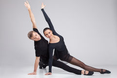 Two ballet dancers practicing on white. Stock Photos