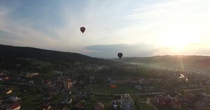 Two balloon flying over the city in the sun. Two balloon fly side by side over a small town with low houses, on the horizon sunshine sets behind the hills, blue stock video