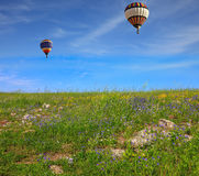 Two balloons fly over field Stock Images