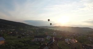 Two balloons are flying to meet the sunset. Aerial view. Two balloon fly side by side over a small town with low houses, on the horizon sunshine sets behind the stock video