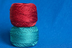 Two balls of a brilliant yarn on a blue background Royalty Free Stock Photo