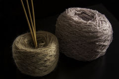Two balls of wool. And needles on a black background. yarn of isolated Royalty Free Stock Images