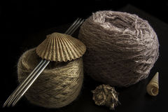 Two balls of wool. Needles and seashells on a black background. yarn of isolated Royalty Free Stock Photos
