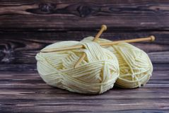 Two balls of yarn for knitting lie on a dark background with knitting needles royalty free stock photos