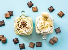 Two banana and kiwi milkshakes in mason jars with creme on top decorated with chocolate pieces. flat lay top view smoothie on blue. Fashion background. creative Royalty Free Stock Photography