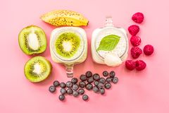 Two banana and kiwi milkshakes in mason jars with creme on top decorated with kiwis, bananas, raspberries and blueberries. flat la. Y top view smoothie on pink Stock Photo