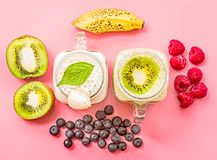 Two banana and kiwi milkshakes in mason jars with creme on top decorated with kiwis, bananas, raspberries and blueberries. flat la. Y top view smoothie on pink Stock Photography