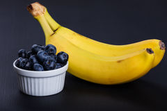 Two bananas and heap of huckleberries.  Royalty Free Stock Photography