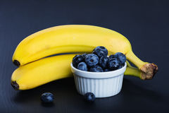 Two bananas and heap of huckleberries.  Stock Photography