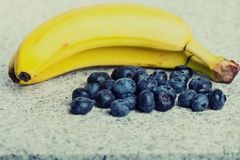 Two bananas and heap of huckleberries.  Royalty Free Stock Image
