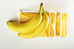 Two bananas located on the sachets banana-flavored porridge, white background Royalty Free Stock Photography