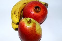 Two bananas, pomegranate and pear stock image