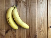 Ripe bananas lie on a wooden table. Two bananas on a wooden background. ripe bananas lie on a wooden table Royalty Free Stock Image