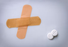 Two bandaids and two pills on a table. Two bandaids and two white pills on a white table Stock Photo