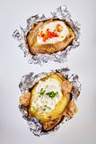 Two barbecued baked potatoes in tin foil. Topped with sour cream and garnished with chopped chives and peppers viewed from overhead still in the foil wrapping royalty free stock photography
