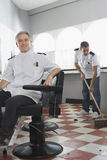 Two Barbers With One Sweeping Floor Stock Photo