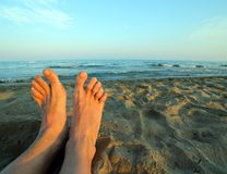 Two bare feet of a man by the sea Royalty Free Stock Image