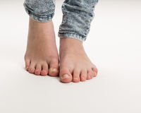 Two Bare Feet Standing On The Floor. Two bare white feet of a girl wearing trousers standing isolated against a white background Stock Images