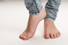 Two Bare Feet Standing TipToe On The Floor. Two bare white feet of a girl wearing trousers standing tiptoeing isolated against a white background Stock Photography