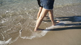 Two barefoot girls walks along the beach near the ocean. Close-up. Camera moves after the girl`s. The waves covers their feet. Two girl friends are walking on stock footage