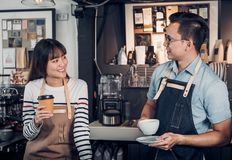 Two barista talking together about tasted of coffee cup with hap. Py emotion at counter bar at cafe.coffee shop business owner concept,Service mind waiter Royalty Free Stock Photo