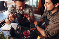 Two bartenders experimenting with creating cocktails Stock Photo