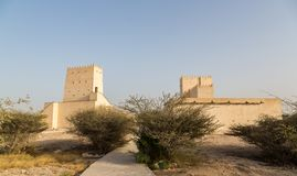 Two Barzan watchtowers fortifications behind desert bushes, Qatar. Middle East. Persian Gulf. royalty free stock images