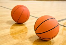 Two Basketball on Court. One basketball sitting on court and second one rolling behind it Stock Photography
