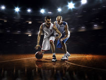 Two basketball players in action. In gym in lights Royalty Free Stock Photo