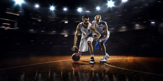 Two basketball players in action. In gym in lights Royalty Free Stock Photography