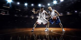Two basketball players in action. In gym in lights Stock Photo