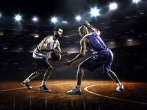 Two basketball players in action. In gym in lights Royalty Free Stock Image