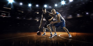 Two basketball players in action. In gym in lights Stock Image