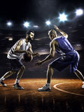 Two basketball players in action. In gym in lights Royalty Free Stock Photos