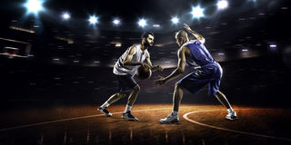 Two basketball players in action. In gym in lights Stock Images